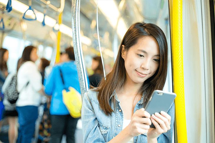 電車でスマートフォンを触る女性