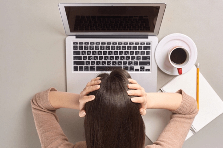 PCを見て頭を抱える女性