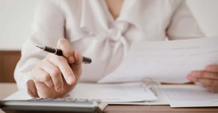 書類片手に計算中の女性