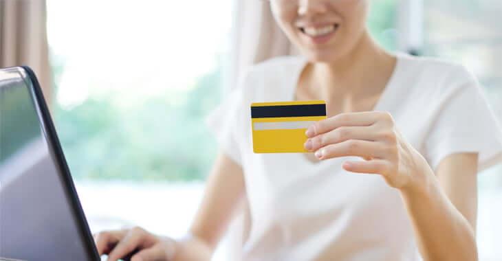 カードを見ながらPC操作する女性