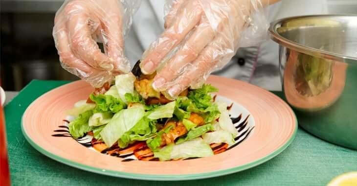 手袋をしてサラダを盛り付ける