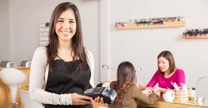 決済端末を持って微笑む女性ネイリスト