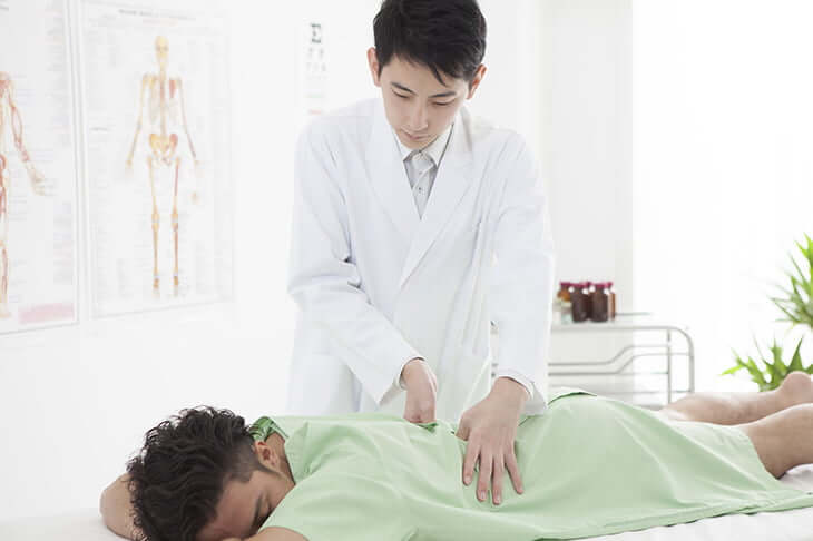 整体院で診察をうける男性