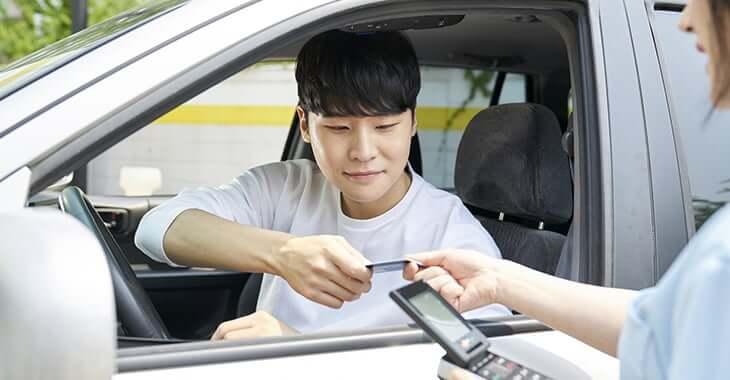車からカードを差し出す男性